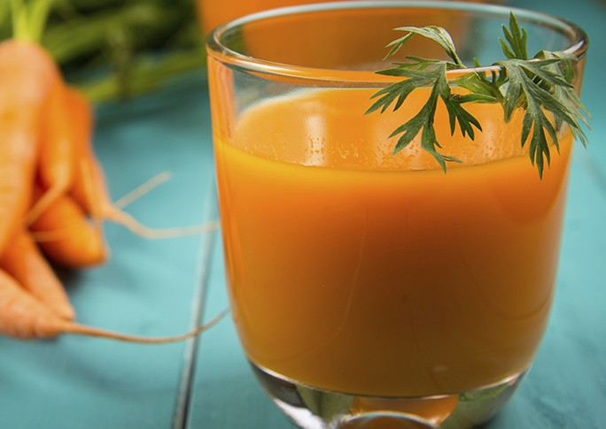 Homemade natural carrot juice in glass on rustic blue wooden table in background