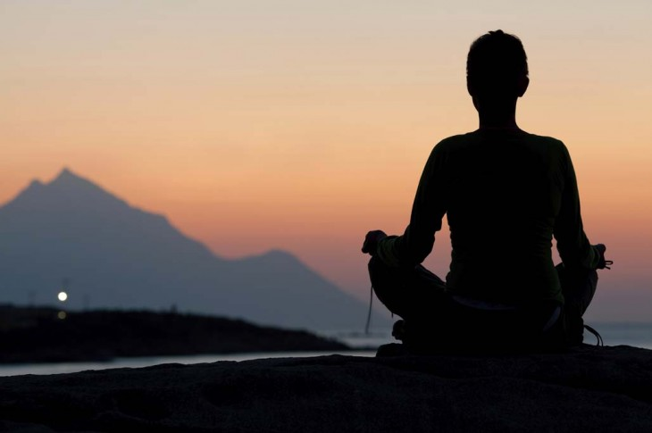 Woman meditating on sunrise