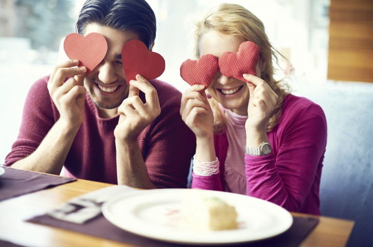 Portrait of cheerful couple posing with hearts