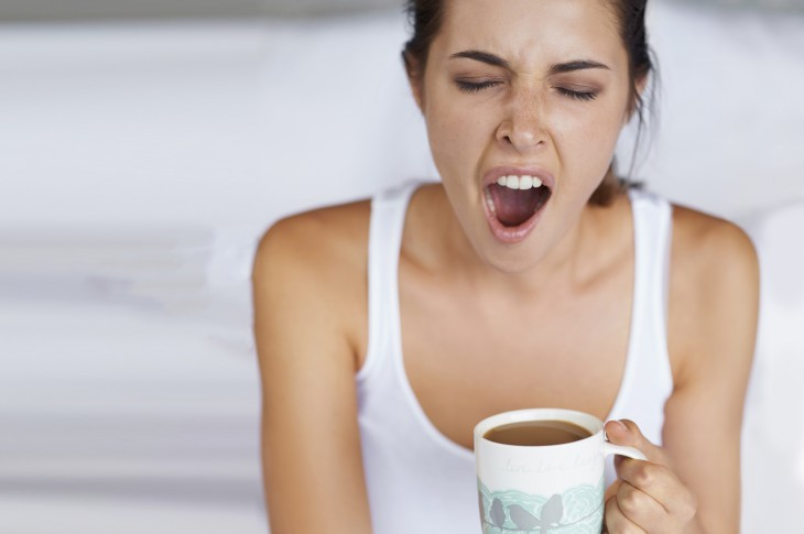 A young woman giving a big yawn while sitting with a cup of coffee in bed