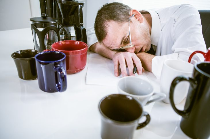A man sits in his office cubicle surrounded by coffee makers and mugs, but apparently the caffeine isn't working since he seems to be falling asleep.  Horizontal.
