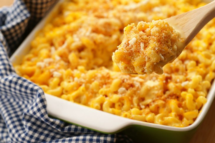 A spoonfull of homestyle baked macaroni and cheese with crispy breadcrumbs and shredded cheddar.  Sharp focus on the contents of the spoon.