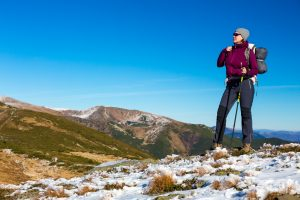Woman Outdoor Hiker Sporty Clothing Staying with Backpack and Walking Poles on Mountain Snowy Trail Enjoying Stunning Landscape View