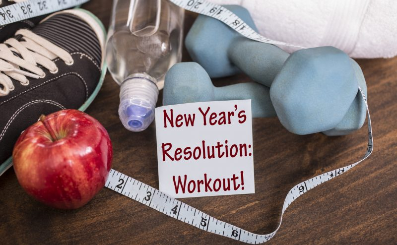 "New Year's Resolution to get healthy in January of the coming year.  Image features: dumbbells, sports shoes, water bottle, apple, towel, tape measure on wooden table.  Adhesive note reading ""New Year's Resolution: Workout!"" in foreground.  Fitness concept."