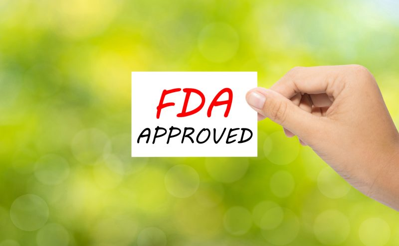 Hand holding a paper FDA APPROVED on green background