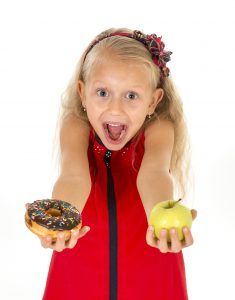 little beautiful female child with blond hair choosing dessert holding unhealthy but tasty chocolate donut and apple fruit in healthy versus unhealthy die nutrition isolated on white background