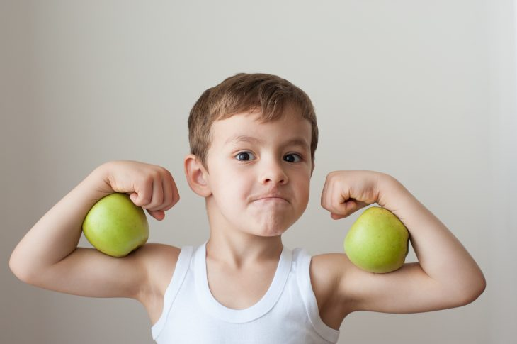 boy with green apples showing biceps face