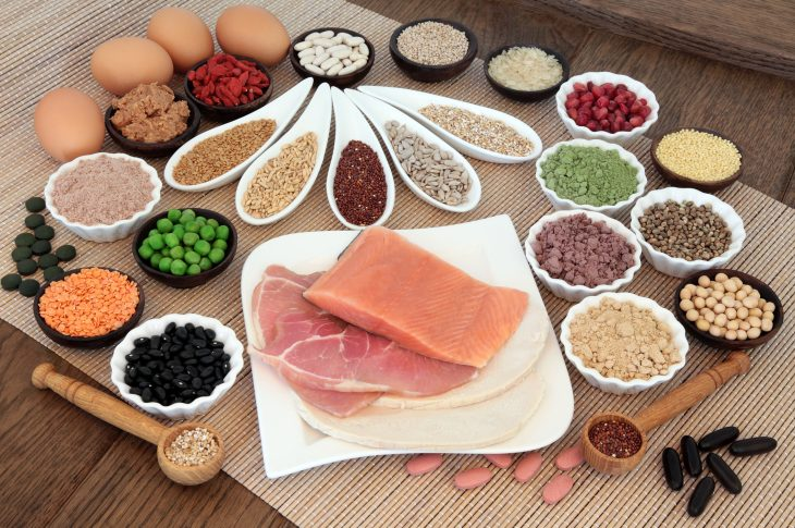 Body building health and super food with high protein meat, fish, eggs, pulses, seeds, nuts, grains, supplement powders, vitamin tablets and fruit.