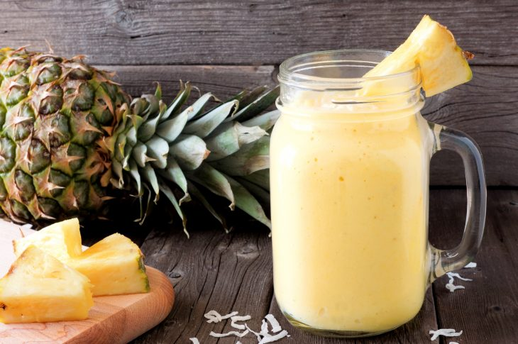 Pineapple smoothie in a mason jar, scene against an old wood background